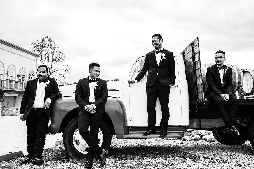 Groomsmen posing on old truck at Morais Vineyards wedding