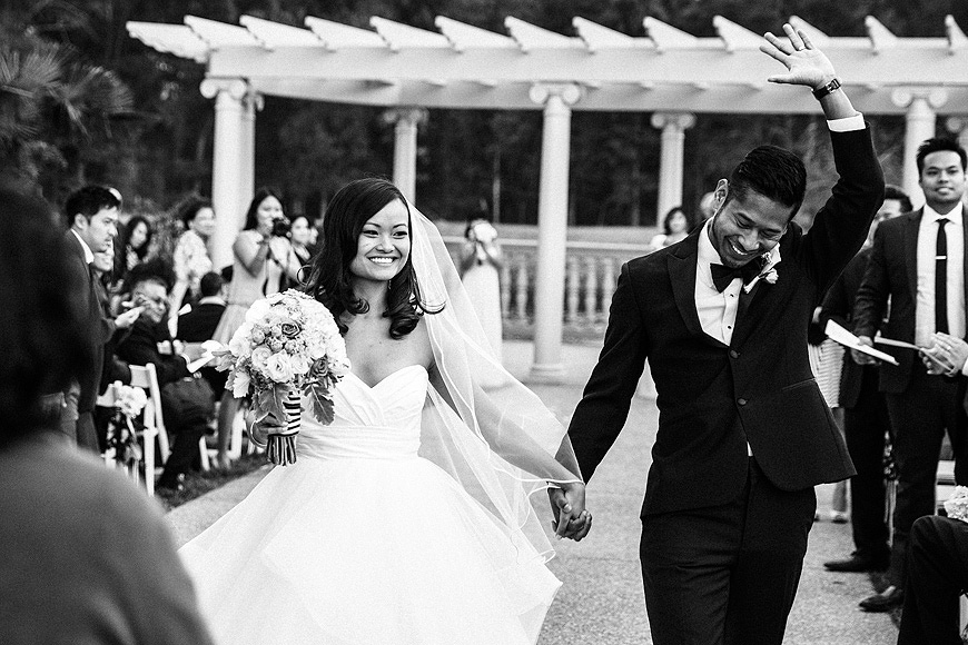 Newly married couple waving to guests at Morais Vineyards wedding