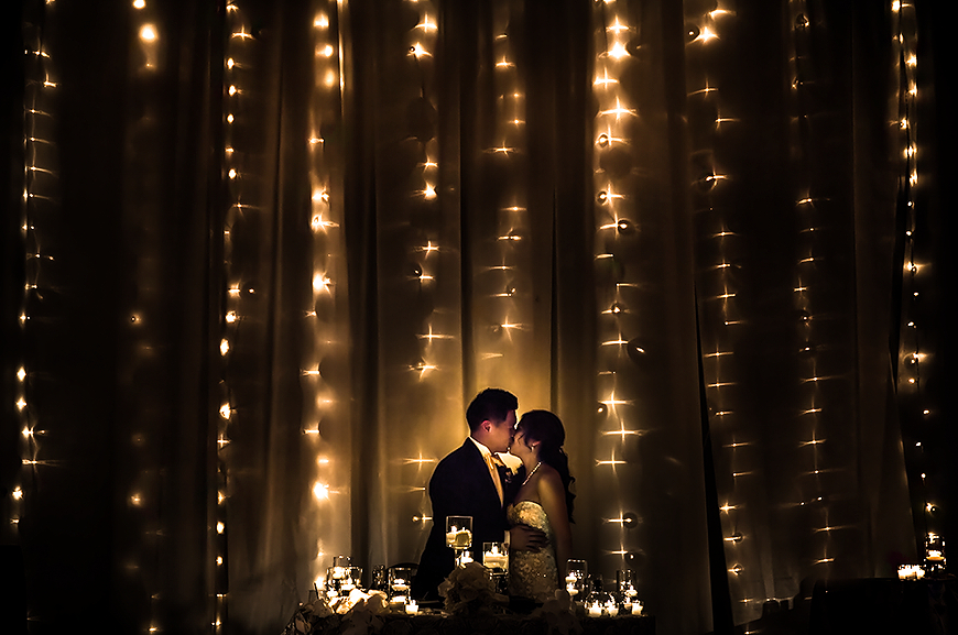 Bride and groom kiss in front of beautiful lights at their Washington DC wedding