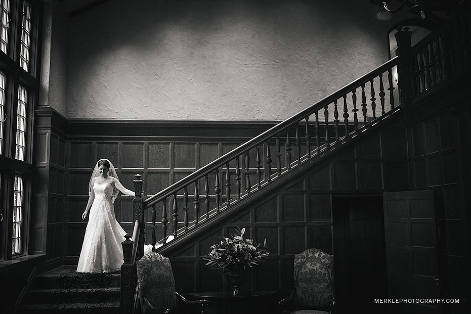 Bride walking down staircase before Greenville Country Club wedding, bathed in beautiful natural window light