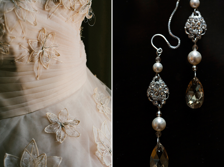 Wedding dress and earrings against black background