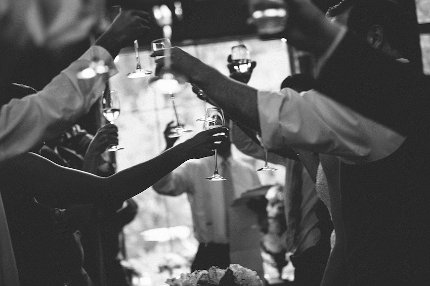 Guests giving a toast with their wine glasses during Woodberry Kitchen wedding