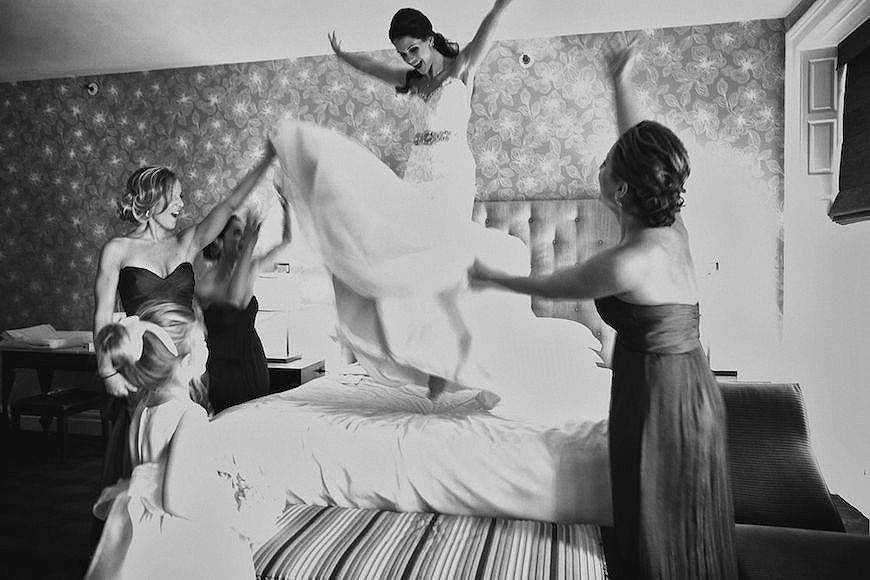 Bride getting ready by jumping on bed before her Hyatt at the Bellevue wedding