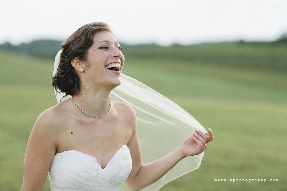 Bride laughing while tugging at her veil at Linganore Vineyards wedding