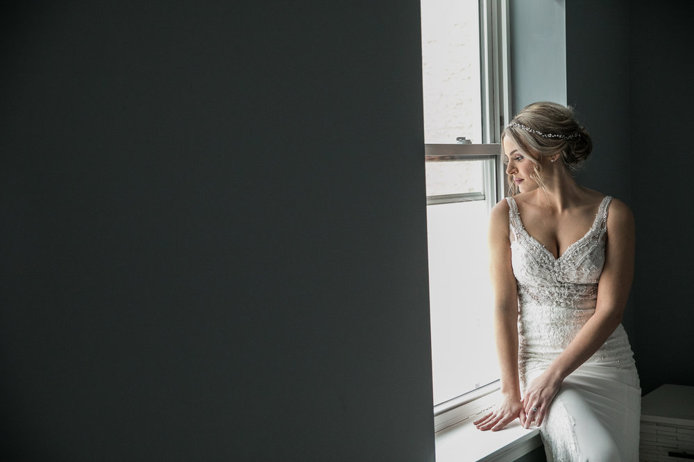 Bride looking out the window before her Cescaphe Ballroom wedding