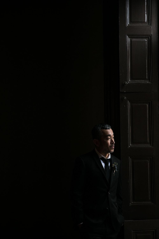 Groom portrait in natural light against dark background
