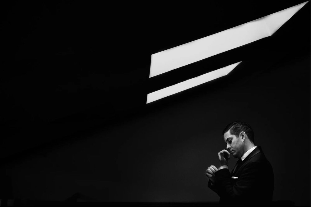 Striking black and white photograph of groom getting ready under a skylight with strong contrast and negative space