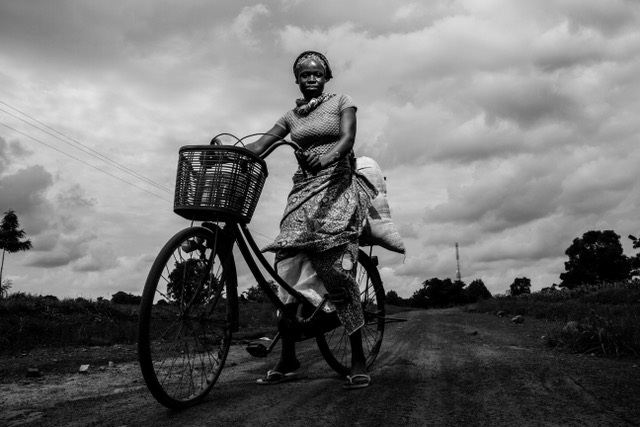 Evans Ahorsu, 2019: Amina is married with four kids. Her husband is a farmer. Amina won't wait for her husband to come back from the farm to take some responsibilities. She picks corn, puts it in a sack on her bicycle and drives to the cornmeal machine whenever her husband is not around. She believes the sharing of labour is the best.
