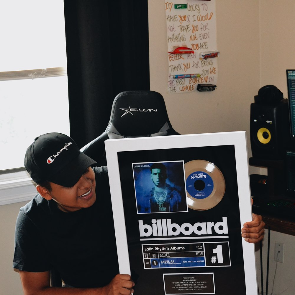 """Armando holding his billboard plaque to commemorate the #1 position for Anuel AA """"Real Hasta La Muerte"""" on the Billboard Latin Rhythm Chart the week of July 28, 2018."""