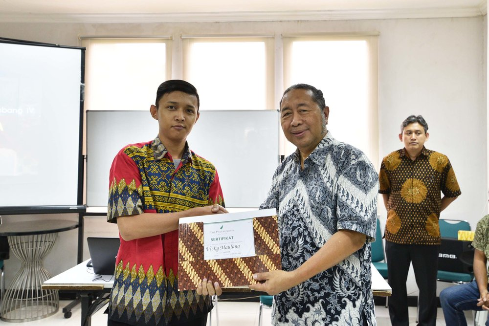 (Mr. Erwinaryo Utoyo handed the certificate to the graduate)