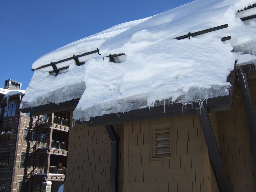 Figure 6:  Snow fences are helping to retain roof snow, but ice dams are still forming at the roof edges and gutters.