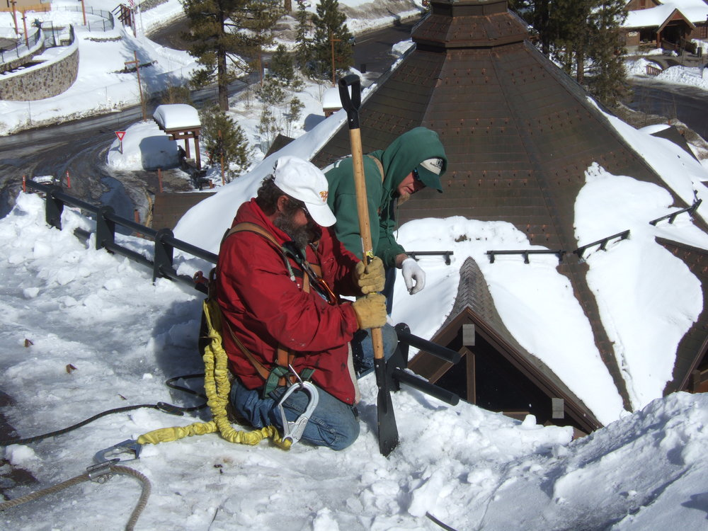 Figure 8:  Workers are chopping ice dams that formed on a ski resort roof six stories up. In addition to safety concerns, this approach can potentially damage the shingles and the underperforming heat cable system.