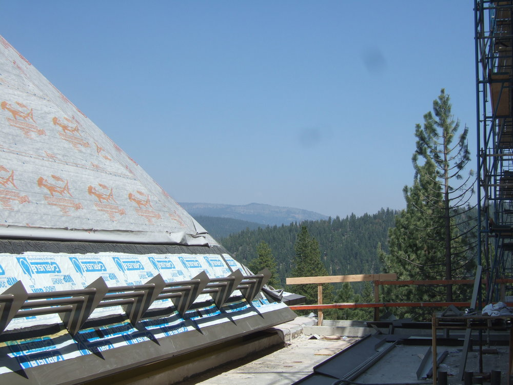 Figure 9:  This is a cold roof under construction with a snow fence, SASM near edges, and high-performance underlayment. The roof will then be shingled. Special metal flashing was designed to minimize water intrusion at the snow fence supports where they are bolted to the structure.