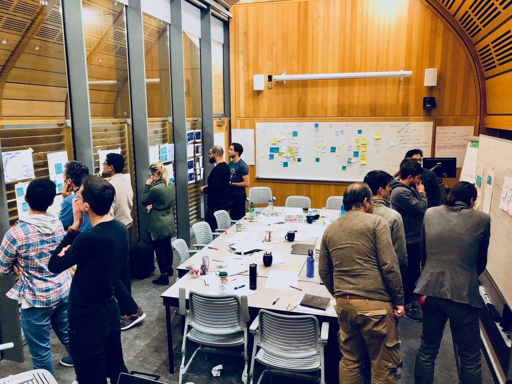 "Idea evaluation - After the brainstorming session, participants walked around the room to check out each other's sketches and ideas. Through a collective decision-making process called ""heatmapping,"" they identified the strongest ideas."