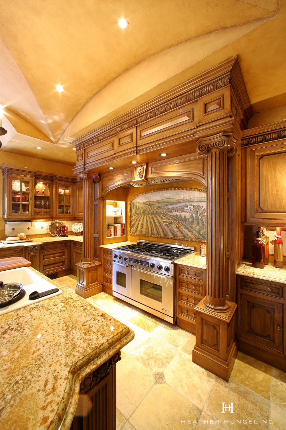 Architectural columns give a Tuscan feel to the large hood design in this luxury Clive Christian kitchen.