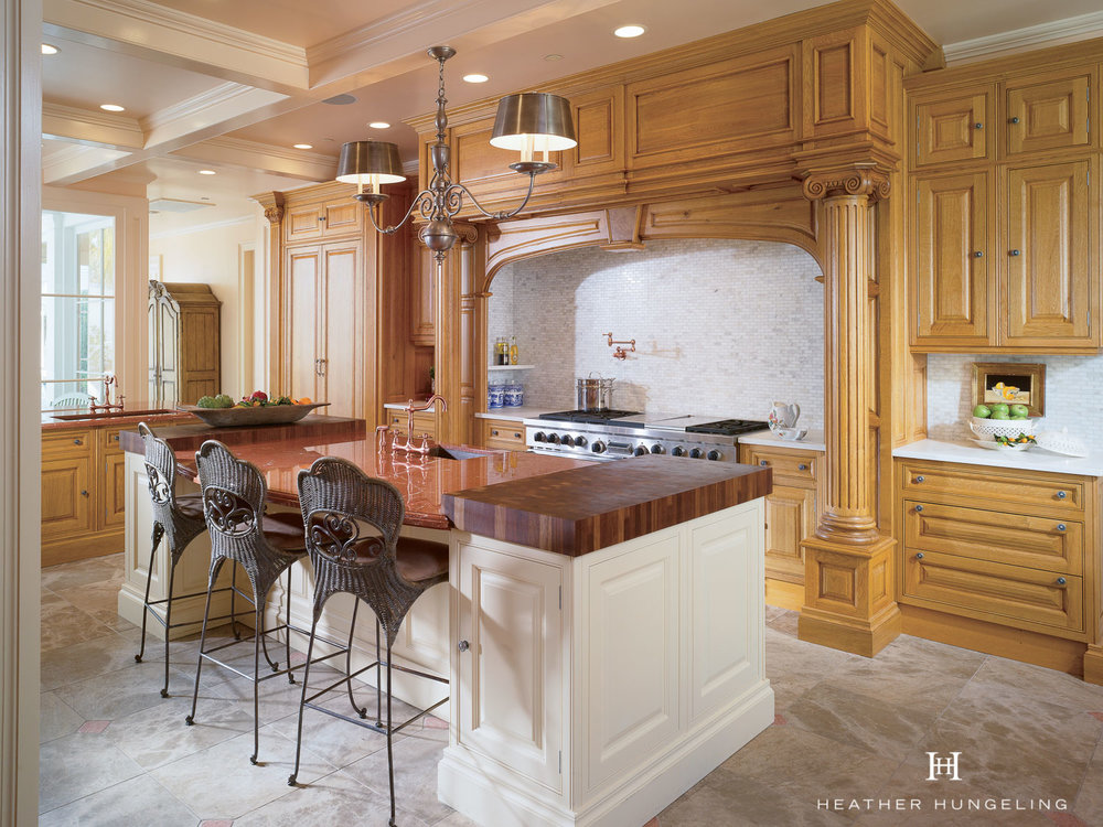 The stately columns on this large hood surround help to balance the length of the room. Cabinetry by Clive Christian. The wood cabinetry is managed growth oak from France, which gives it a very different look to the busier oak we have here in the U.S. The painted cabinetry is Linen White.