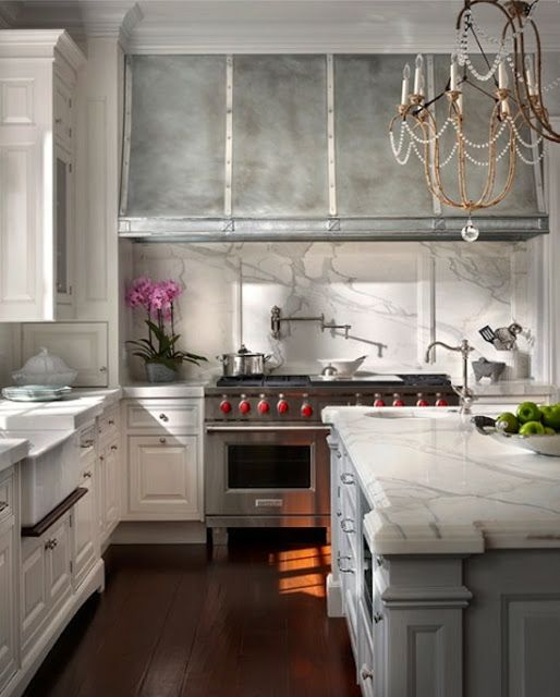 A nickel silver hood design looks stunning with white calacatta marble backsplash.  Source:   Obrien Harris