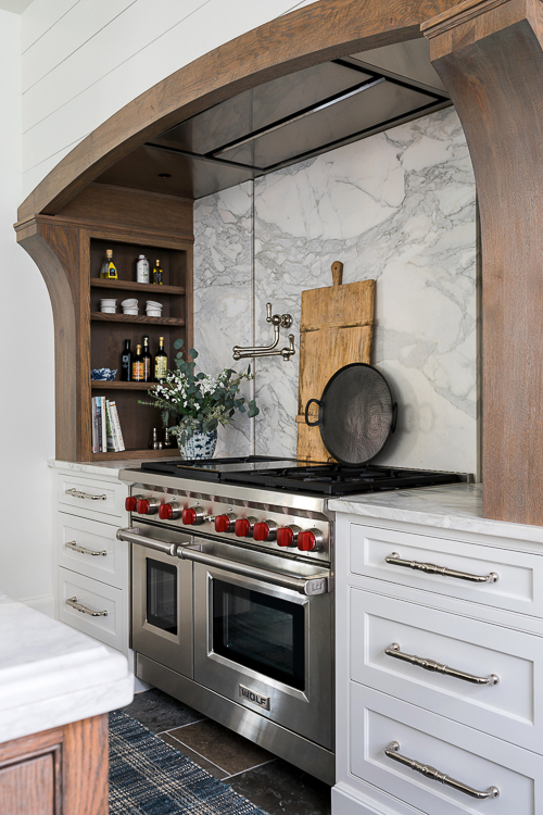 A creative range hood design perfectly suited to the modern farmhouse vibe, showcasing the beauty of the wood mantle against crisp white shiplap paneling.  Source:  Sherry Hart Designs