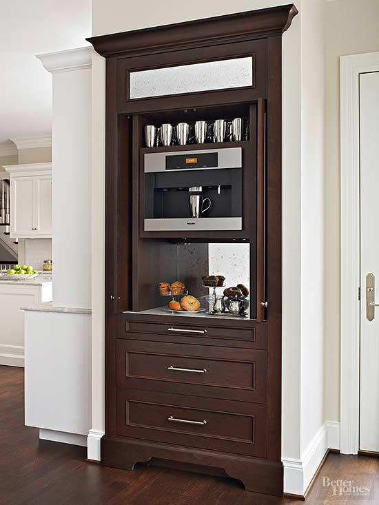 A tall walnut cabinet with pocket doors makes an attractive place to store the coffee station. A built-in Miele coffee maker and a mirrored back panel makes the cabinetry pretty to look at even when the doors are open. Source:  BH&G