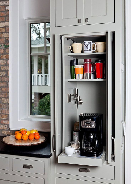 A small, concealed, coffee station idea for inside of a narrow custom cabinet with pocket doors. A pull-out shelf and a water dispenser add to the convenience of this design. Grey cabinetry. Black counters. Brick wall.  Source:      In Detail Interiors