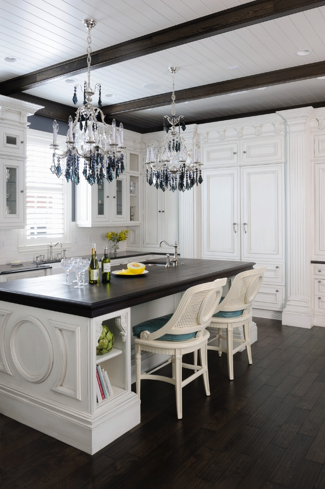 This luxury white kitchen creates drama by contrasting with darker materials, such as the Wenge wood countertop, dark beams, and hardwood floors.