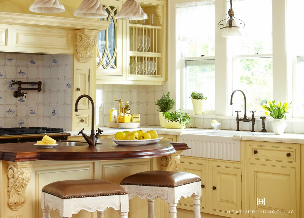 Using a wood countertop on the island and then using marble on the perimeters is a great solution. Wood is fairly easy to care for (just don't cut on it) so use it on your harder working areas and then enjoy the beauty of the marble on the perimeter cabinetry.