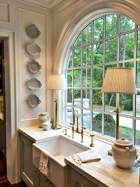 This large kitchen window design idea suits the style of the cabinetry so well. It is dressy and elegant and would be very easy to incorporate into a remodel. I appreciate how they made the window low to the countertop in order to keep the visibility out of the window.