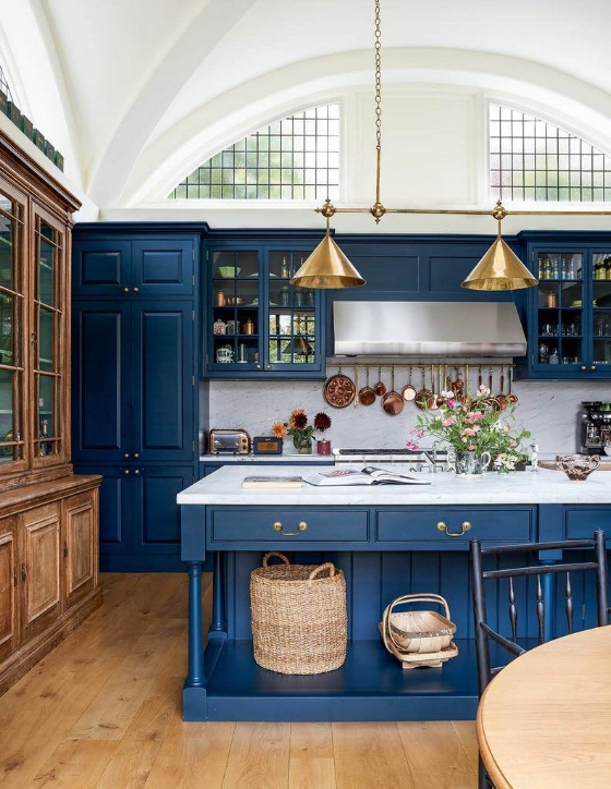 A large kitchen window design idea utilizing a large arched window above the cabinetry instead of over a kitchen sink. While tall ceilings are needed to pull this off, this idea gives you full use of the wall for cabinetry if storage is a priority.  Source: Ben Pentreath.