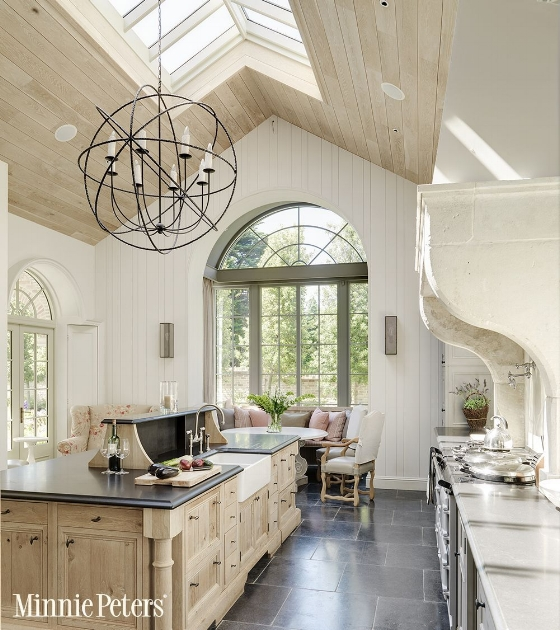 Consider how your large kitchen window design idea will be impacted by the type of light you receive throughout the day. This kitchen features windows, glass doors, and skylights to incorporate a variety of sunlight.  Source: Minnie Peters