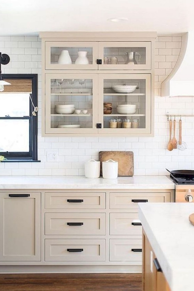 How to Make Your Kitchen Beautiful with Pretty Cabinet Details, Part 1 (Cabinet Interiors).  Backless glass cabinets are a new take on the open shelves trend. In this kitchen, the wide glass doors appear almost weightless and the tile (and the contents of the cabinetry) are allowed to take center stage. #kitchencabinetdetails