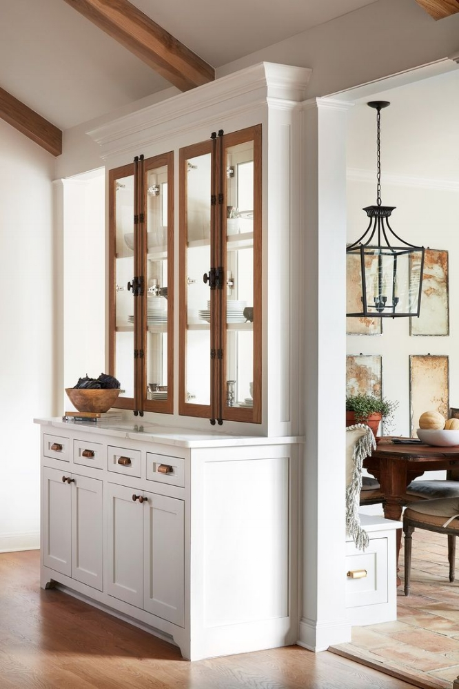 """How to Make Your Kitchen Beautiful with Pretty Cabinet Details, Part 1 (Cabinet Interiors).  Joanna Gaines revitalizes the old """"double sided glass cabinet"""" trick of the '80s. As beautiful as it is functional, this furniture-style hutch allows light to pass through a needed room divider between the kitchen and the breakfast area. #kitchencabinetdetails"""