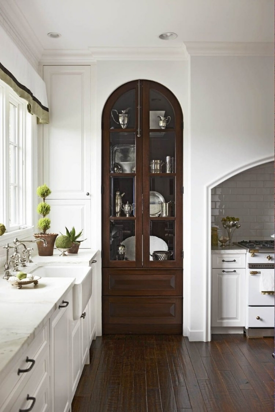 Arched glass cabinet doors give this tall display unit extra interest. Your eyes are naturally drawn to curves in a kitchen, which is usually full of straight lines and rectangular shapes.