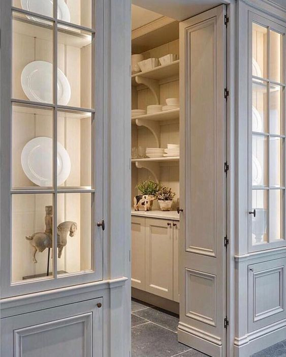 Consider using a pair of glass cabinet doors to flank the entrance to a butler's pantry. What a pretty statement this arrangement (by Minnie Peters) makes in the hallway.