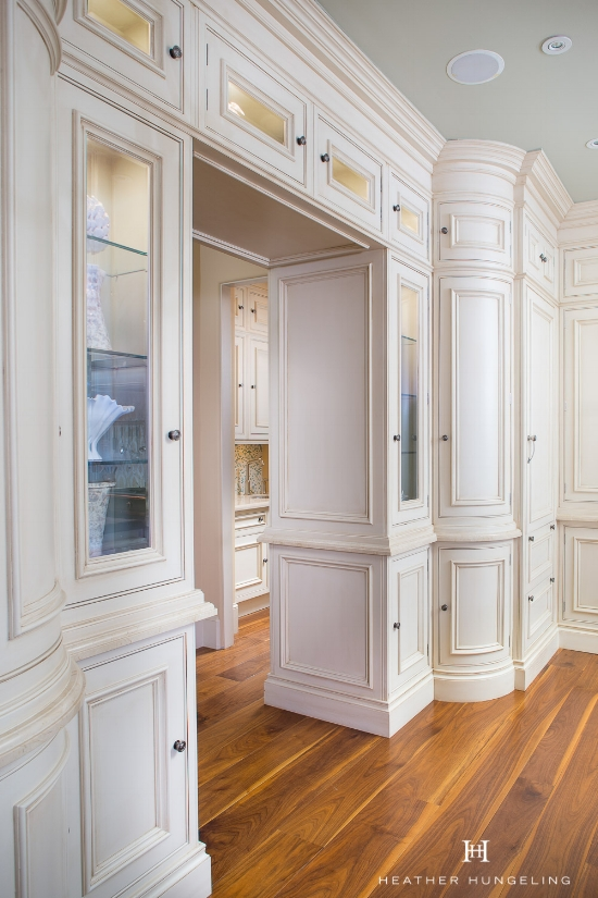 Curved cabinet door styles provide interest and character to the entrance of this kitchen. Clive Christian cream painted cabinetry, designed by Heather Hungeling.