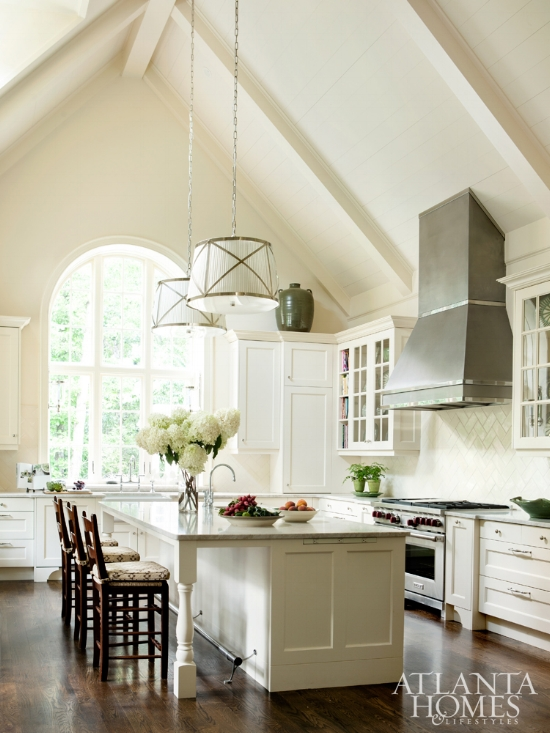 Vaulted ceilings certainly help to make this room with cream kitchen cabinets feel bright and airy, but so does painting the cabinetry, trim, and walls a consistent color.
