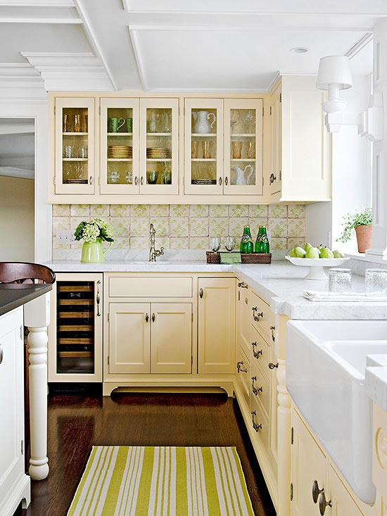 Cream kitchen cabinets are contrasted nicely with white marble, a white farmhouse sink, and the white paneled ceiling.