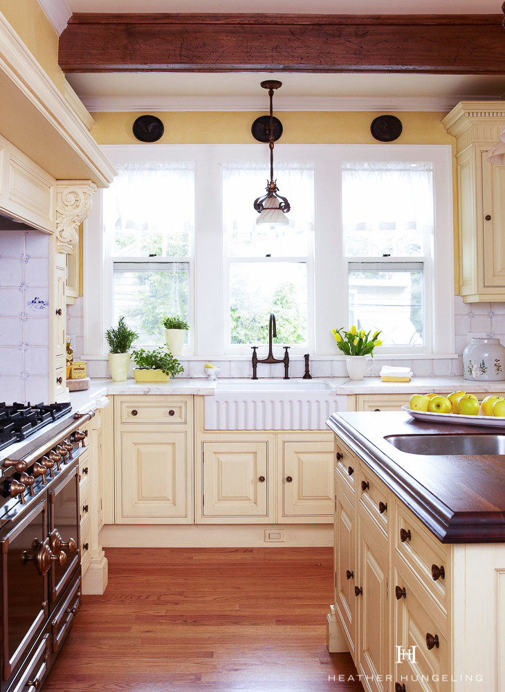 A fluted farmhouse sink looks a little a little dressier than the typical apron sink and pairs well with the black CornuFe range in this vintage kitchen. Antique Cream painted cabinetry by Clive Christian.