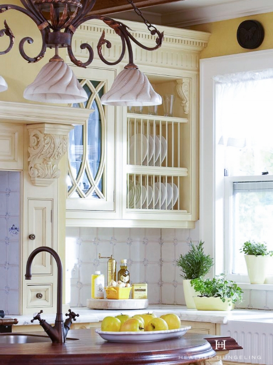The homeowner of this English kitchen design (featuring Clive Christian cabinetry) loved the vintage appeal of a plate rack tucked into the corner, next to the sink.
