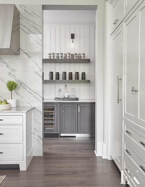 Marble applied to the entire wall behind the range makes a striking statement. Love it juxtaposed against the v-groove boards of the pantry. See more  Kitchen Marble Ideas  for ways to incorporate more of that beautiful material you love.