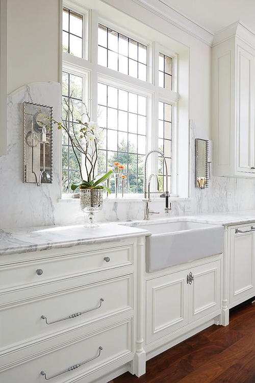 A marble slab, applied to the wall around this window, gracefully arches upward to play host to two mirrored sconces. See more mesmerizing  Kitchen Marble Ideas  to use in your next kitchen.