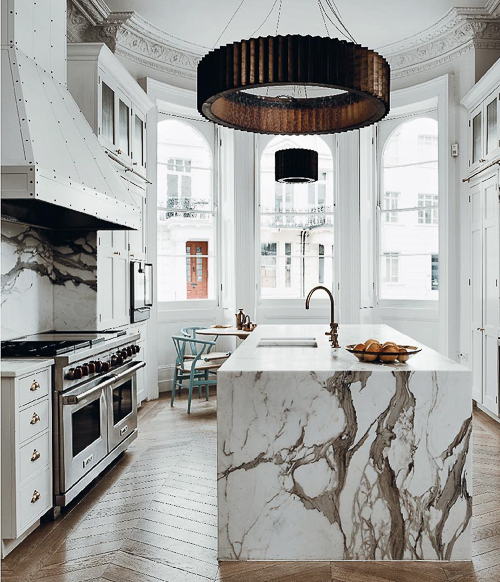A stunning marble slab is used to create a waterfall countertop for a kitchen island. See more Kitchen Marble Ideas that you can use for your next kitchen project.