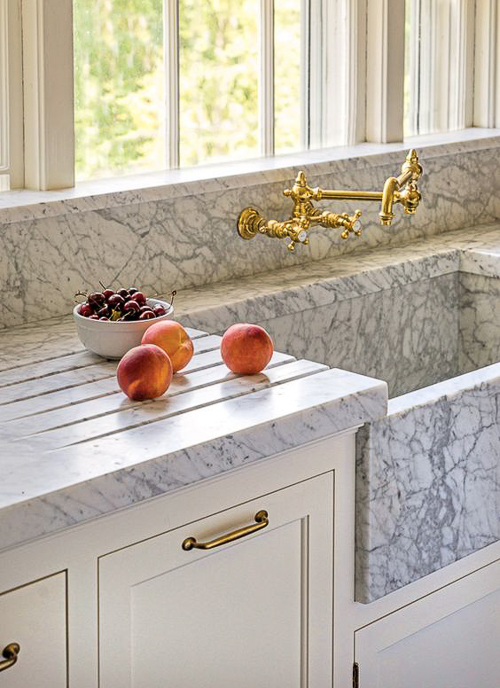 Grooves are cut into the marble surrounding this marble sink. The grooves are a nice feature, regardless of what counter material is selected, as they help to eliminate the splashes and puddles that accumulate around the sink. Kitchen Marble Ideas.