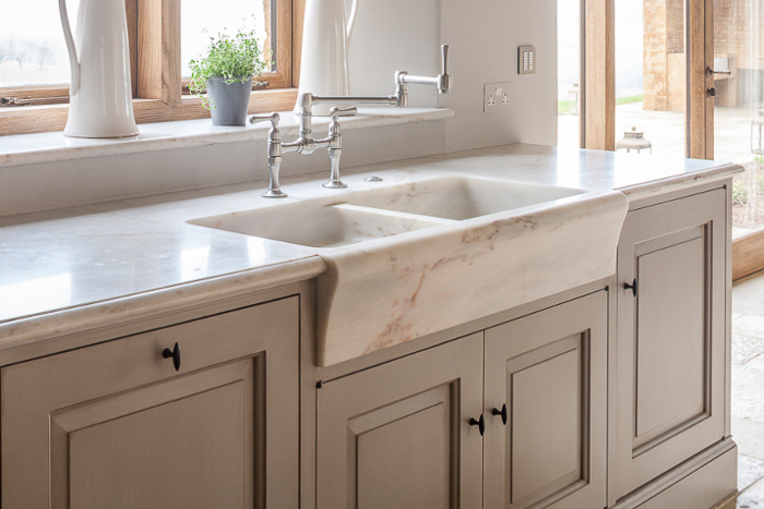 A curvy, apron front marble sink looks quite at home in this English kitchen. Kitchen Marble Ideas.