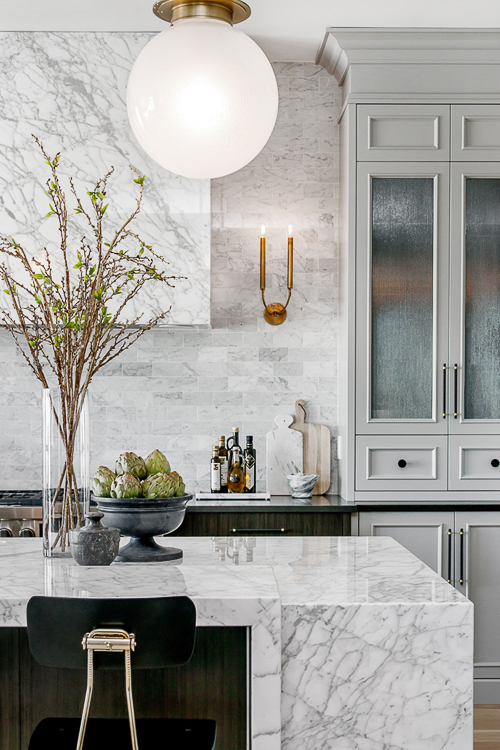 A marble range hood virtually disappears against the backdrop of marble tile. A smart way to capture that light and open (sans upper cabinets) look that is so prevalent today. Kitchen Marble Ideas.
