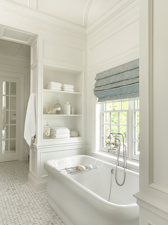 """A bathroom with paneling is pretty high up on my """"swoon-worthy"""" list. However, this bathroom surpasses that mark by integrating some cool shelving into the paneling around the tub, creating a truly bespoke and luxurious feeling. See other Master Bathtub Ideas. #luxurybathrooms, #traditionalbathroom, #whitebathrooms"""