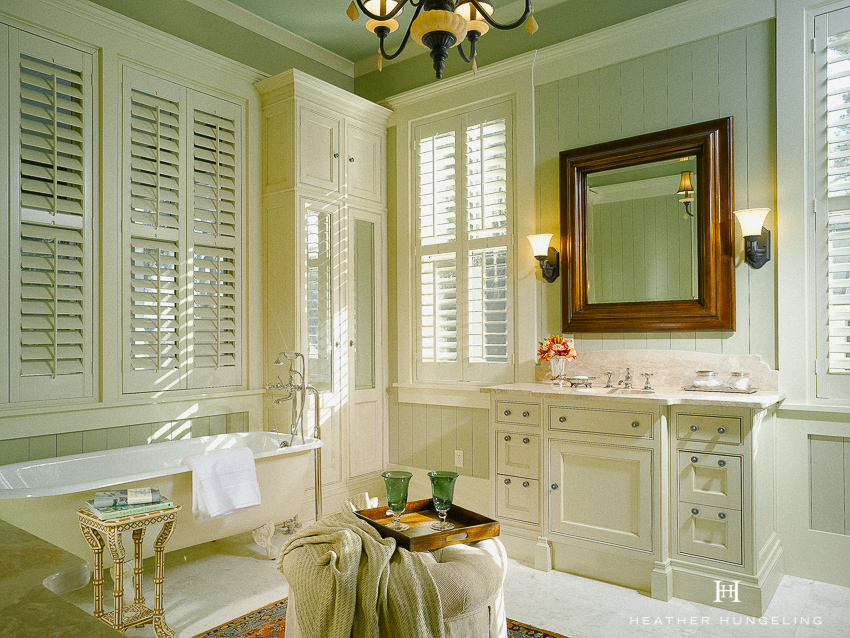 A Lowcountry home often showcases a soothing palette of greens and blues, such as this Sage Green bathroom with ivory cabinetry by Clive Christian. #luxurybathroomdesigns, #clivechristian, #traditionalbathroom