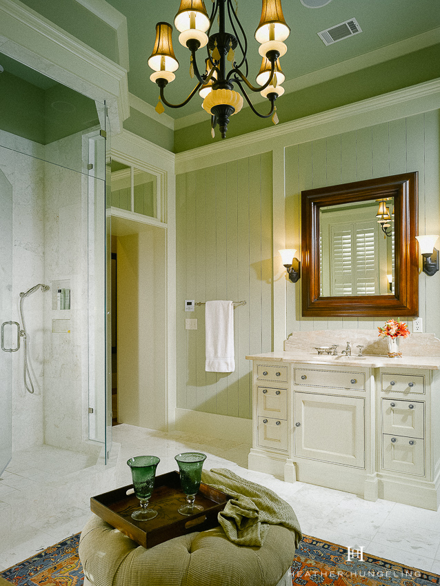 A Lowcountry bathroom in Palmetto Bluff features Sage Green vertical wood planks on the wall and ivory cabinetry. #luxurybathroomdesigns, #clivechristian, #traditionalbathroom