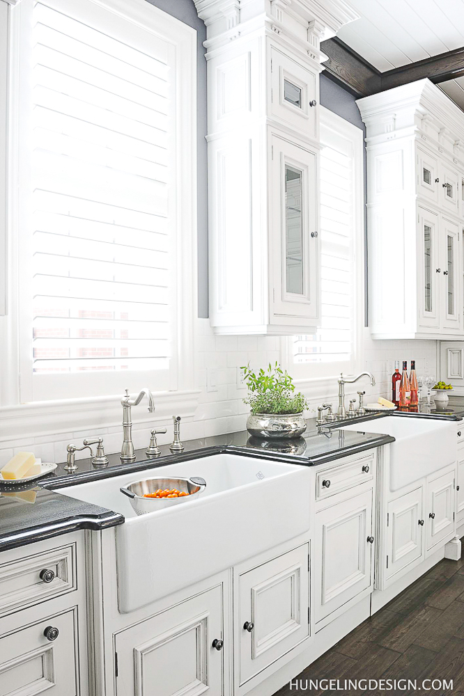 Kitchen Cabinetry Design Mistake #3: Not paneling the dishwasher(s). A dishwasher is not a pretty appliance and visually breaks up the continuity of your cabinetry. Notice how seamlessly the dishwasher appears in this kitchen? (It's between the two sinks). #kitchencabinetrydesign #luxurykitchendesigns, #clivechristian, #traditionalkitchens,