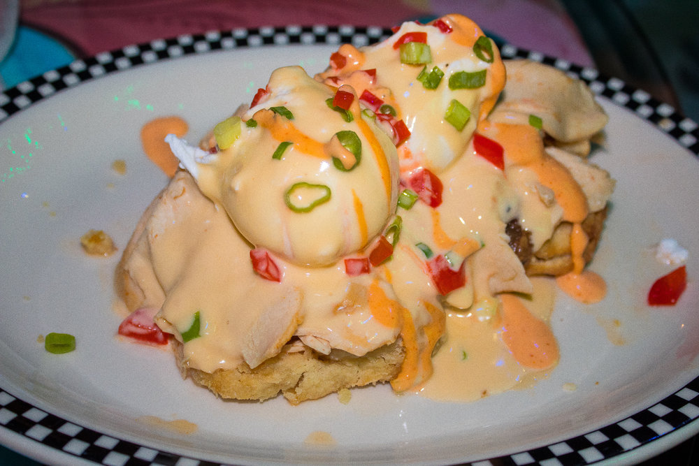 Hobbits Salty Pork Benedict - bacon, fig jam, brie cheese, poached egg, buttermilk biscuits, and hollandaise sauce