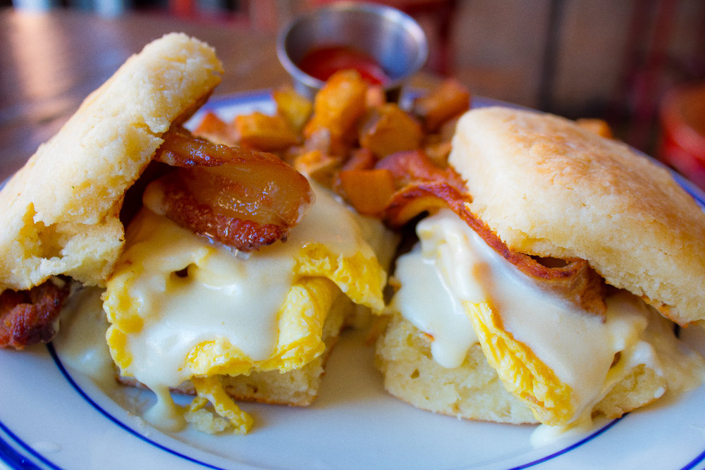 Biscuit Bacon Sammies - Two biscuits, scrambled eggs, jalapeño, bacon, mournay sauce, side of breakfast potatoes